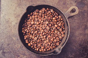 Frying pan with coffee beans during roasting