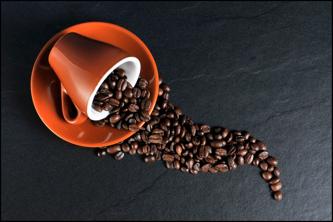 Coffee beans and ceramic mugs on black surface
