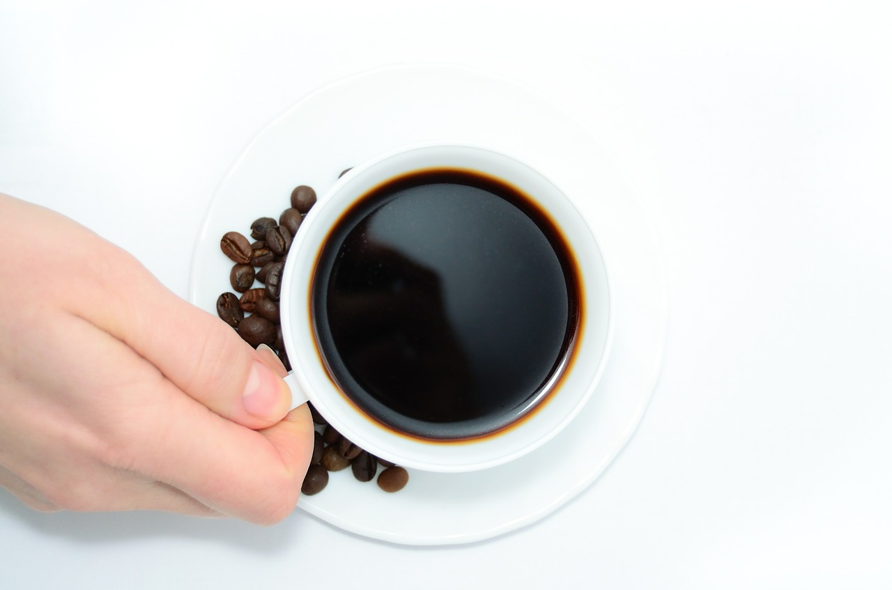 person holding a cup of coffee with coffee beans