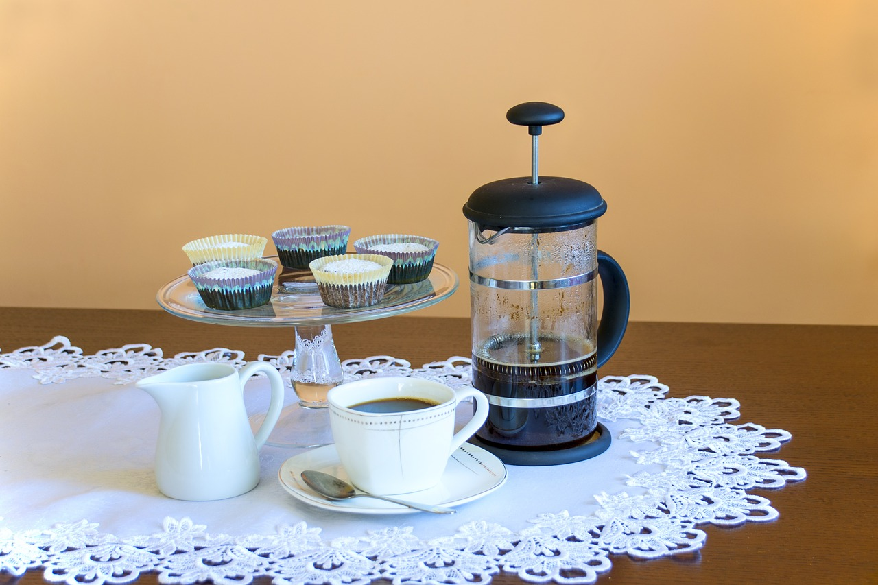 french press vs. aeropress on a table with cupcakes